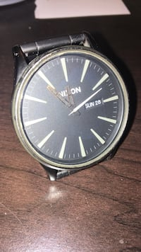Gold-colored Nixon analog watch with black sports band