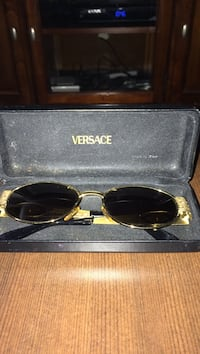 gold-colored-framed Versace sunglasses with case