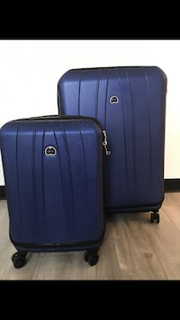 two blue hard-side Delsey luggages