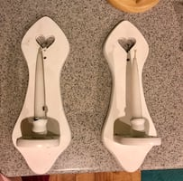 Two white wooden sconce candle holders with two white candle sticks