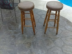 two brown wooden base brown leather padded stools