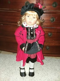 red and black dressed blonde haired female porcelain doll