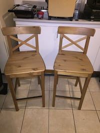 two brown wooden bar chairs