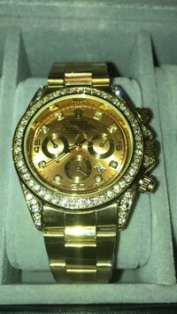round gold Rolex chronograph watch with gold link bracelet