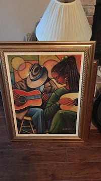 brown wooden framed man wearing hat and woman in green dress playing guitarsd