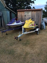 two purple and yellow personal watercraft