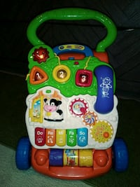 toddler's green and white Vtech learning walker