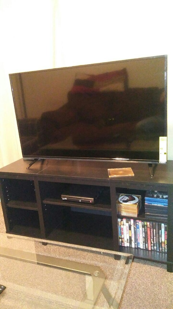 black flat screen TV with brown wooden TV stand