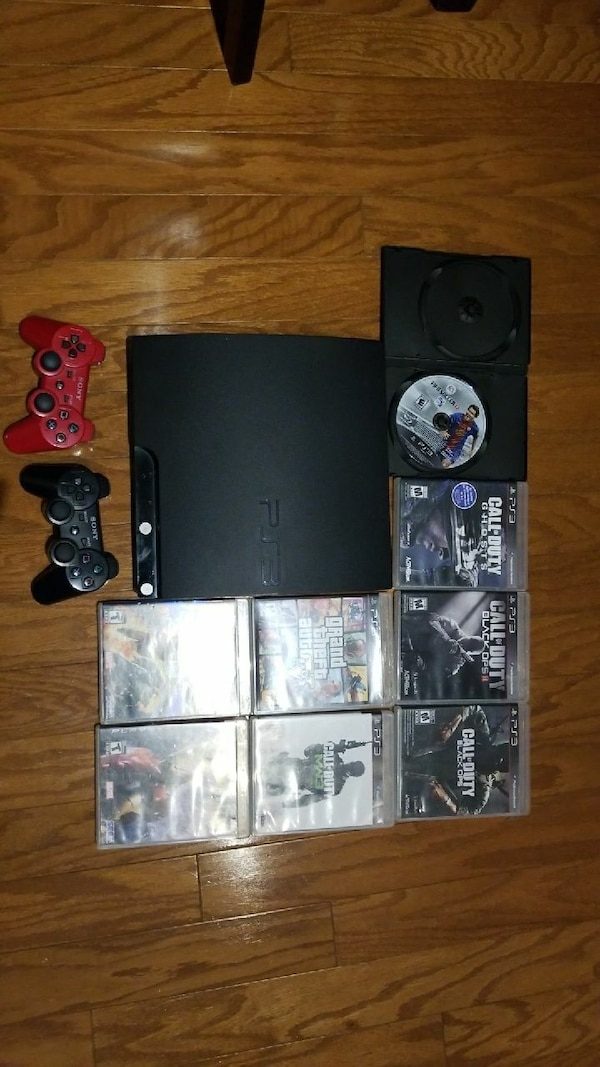 black Sony PS3 slim console with controllers and g