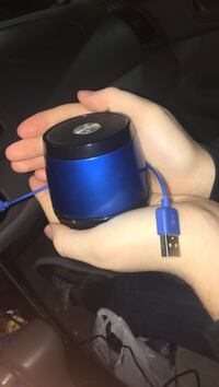round blue and black portable bluetooth speaker