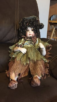 Brown haired female porcelain doll with green and brown outfit