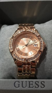 round gold-colored Guess analog watch with link strap