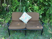 black steel framed brown cushioned loveseat