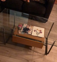 Glass coffee table has silver legs and storage