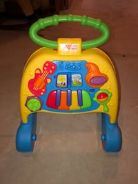 toddler's yellow, blue, and green Fisher-Price learning walker