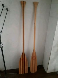 two brown wooden boat paddles