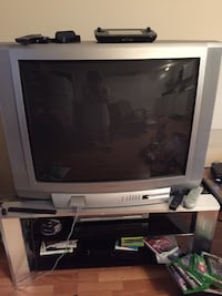 gray CRT TV with gray wooden TV stand Laval, H7A 3L8