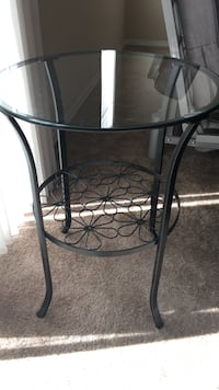 Round end table with clear glass top and black daisy pattern steel base Santa Cruz, 95060