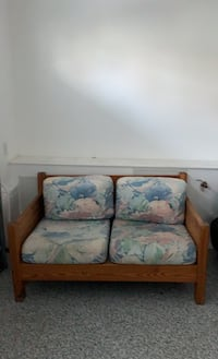 Solid oak love seat with pastel cushions