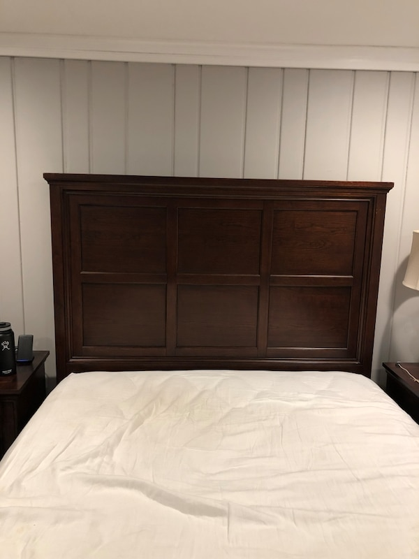 brown wooden bed frame with white bed sheet 6aa437f7-26ff-4701-ade5-28703f5e6e3b