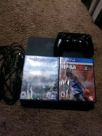 black Sony PS4 console with controller and game cases