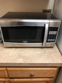gray and black Oster microwave oven