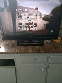 black flat screen TV with black wooden TV stand Calgary, T2B 3C4