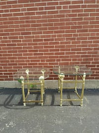two square gold-colored metal-framed glass side tables