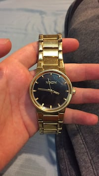 round gold-colored Nixon analog watch with link bracelet Saint Louis, 63125