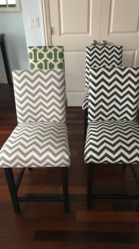 Four white-and-black, grey and white chevron and green and white pattern dining chairs with wooden base