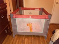 toddler's red and grey travel cot