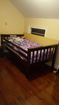brown wooden bed frame with pink and blue bed sheet set