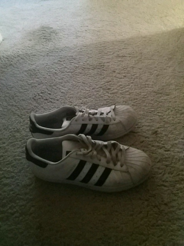 pair of white adidas low-top sneakers