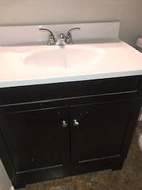 white and black ceramic sink with cabinet