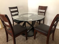 round glass top table with four chairs dining set. Tempered glass. Solid round wood base. Chairs are wood with soft leather seats.  Moorpark, 93021
