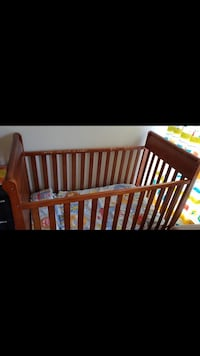 baby's brown wooden crib 23 km