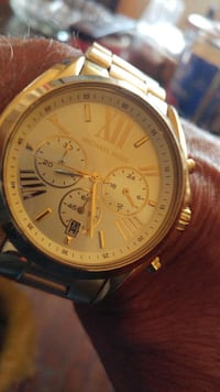round gold chronograph watch with black leather strap