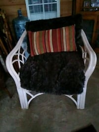 Wicker chair with faux fur cushions.