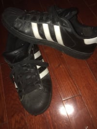 Pair of black adidas superstar shoes 556 km
