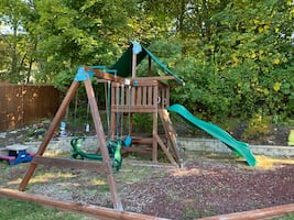 Swing set with glider, slide, rock wall, picnic table, and fort!
