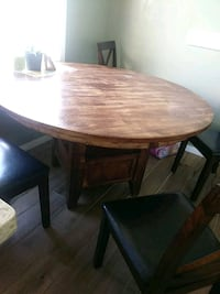 round brown wooden table with 4 chairs
