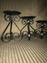 three black metal candle holders
