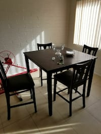 rectangular black wooden table with four chairs dining set