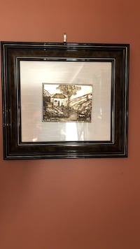 Brown wooden framed painting of house near mountain.