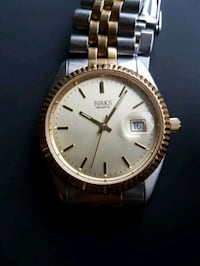 round gold-colored Birks analog watch with link bracelet