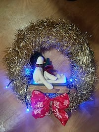 green tinsel wreath with bow, snowman and lights