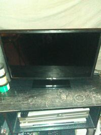 black flat screen TV with brown wooden TV stand Long Beach, 90813