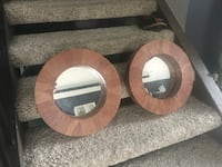 two round brown wooden framed leaning mirrors