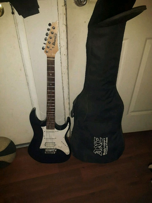 black and white Ibanez electric guitar with gig case