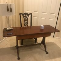 brown wooden desk with black rolling chair